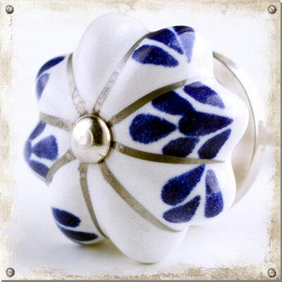 Vit knopp med blå blad och silverfärgade strimmor