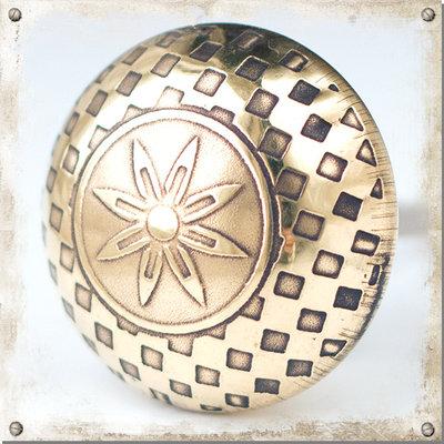 Guldfärgad metallknopp med vackert mönster