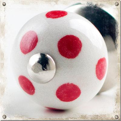 Liten vit knopp i porslin med röda prickar